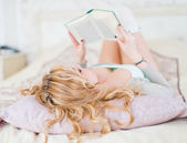 woman reading on a bed  — Stock Photo