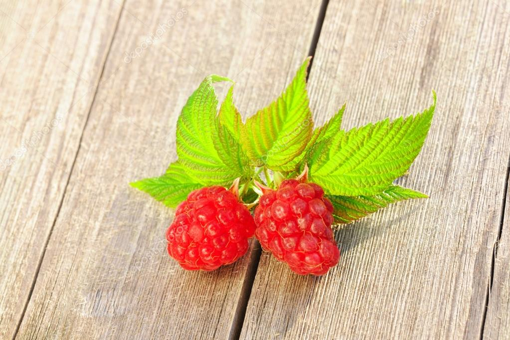 Raspberry with leafs on wooden table — Stock Photo #13490231