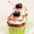 Cupcakes with whipped cream and cherry — Stock Photo #13664343