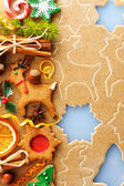 Christmas spices and cookies over gingerbread dough — Stock Photo