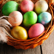 colored easter eggs in basket — Stock Photo