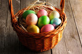 Colored easter eggs in basket — Stok fotoğraf