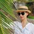 Woman in sunglasses near palm tree — Stock Photo