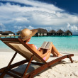 Stock Photo: Young woman reading a book at beach