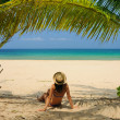Woman at beach under palm tree — Stock Photo #21613235