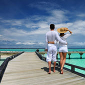 Couple on a beach jetty at Maldives — Stok fotoğraf