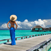 Woman on a beach jetty at Maldives — Stok fotoğraf