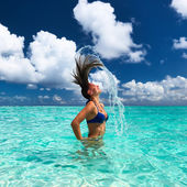 Woman splashing water with hair in the ocean — Stock Photo