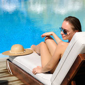 Woman relaxing at the poolside — Stock Photo