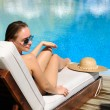 Woman relaxing at the poolside - Stockfoto