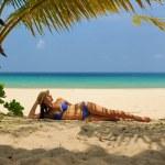 Woman at beach under palm tree — Stock Photo #23467408