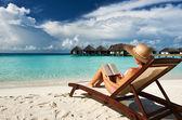 Mladá žena s knihou na pláži — Stock fotografie