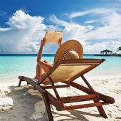 Junge frau, die ein buch am strand lesen — Stockfoto