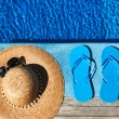 Blue slippers and hat by a swimming pool — Stock Photo #24150825