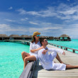 Couple on a beach jetty at Maldives — Stock Photo #24150913