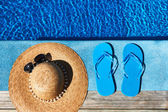Blue slippers and hat by a swimming pool — Stock Photo