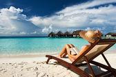 Joven leyendo un libro en la playa — Foto de Stock