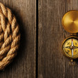 Antique compass and rope over wooden background — Stock Photo