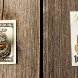 Stock Photo: US and euro money over wooden background