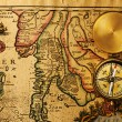 Antique compass over old map — Stock Photo #26705771