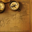 Antique compass over old map — Stock Photo #26705825