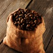Coffee beans in bag on table — Stock Photo #27010593