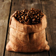 Coffee beans in bag on table — Stock Photo #27010597