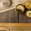 Stockfoto: Antique compasses over old map