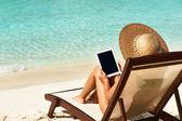 Mujer joven con tablet pc en la playa — Foto de Stock