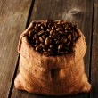Coffee beans in bag on table — Stock Photo #27621511