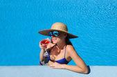 Mujer en la piscina con un cóctel cosmopolitan — Foto de Stock