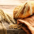Rye spikelets and bread on wooden background — Stock Photo