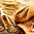 Rye spikelets and bread still life on wooden background — Stock Photo