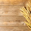 Stock Photo: Rye spikelets over wooden background