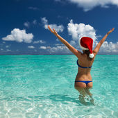 Woman in santa's hat at beach — Stock Photo