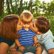Happy parents kissing their child outdoors — Stock Photo #32094761
