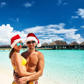 Couple in santa's hat on a beach at Maldives — Foto Stock