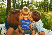 Happy parents kissing their child outdoors — Stock Photo
