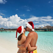Couple in santa's hat on a beach at Maldives — Stok fotoğraf