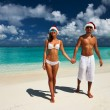 Couple in santa's hat on a beach — Stock Photo