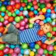 Stock Photo: Happy child playing with colorful plastic balls