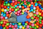 Happy child playing with colorful plastic balls — Stock Photo