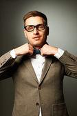 Confident nerd in eyeglasses adjusting his bow-tie — Stock Photo