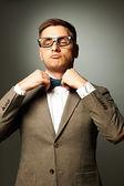 Confiant nerd à lunettes, ajustant son noeud-papillon — Photo