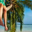 Woman sitting on a palm tree at tropical beach — Stock Photo #40798385