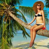 Frau sitzt auf einer palme — Stockfoto