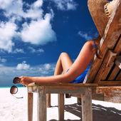 Kobieta na plaży trzymając okulary — Zdjęcie stockowe