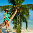 Woman sitting on a palm tree at tropical beach — Stock Photo #41644651