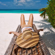 Woman at beach lying on chaise lounge — Stock Photo