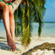 Woman sitting on a palm tree at tropical beach — Stock Photo #41644867